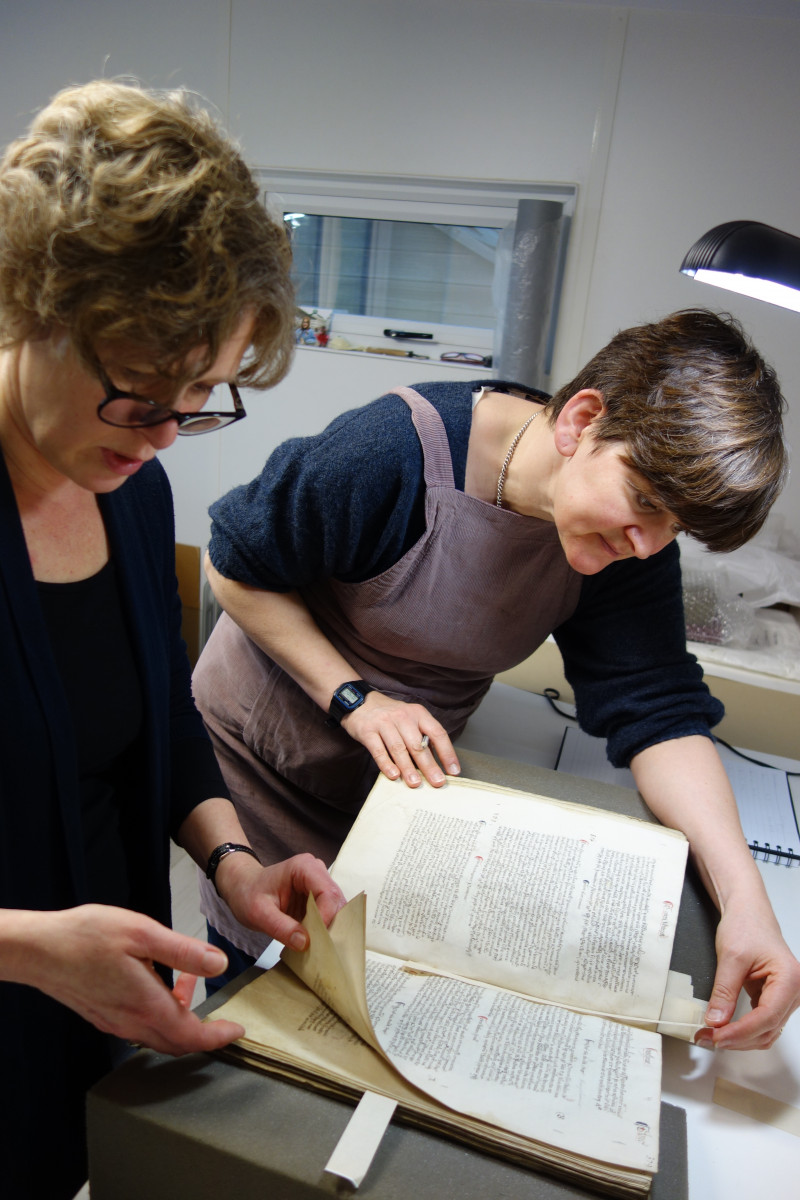 Conservators inspecting the manuscript
