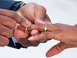 A hand placing a wedding ring on another person's hand