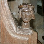 Carved head of a man on back pew.