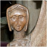 carved head of a woman on back pew.