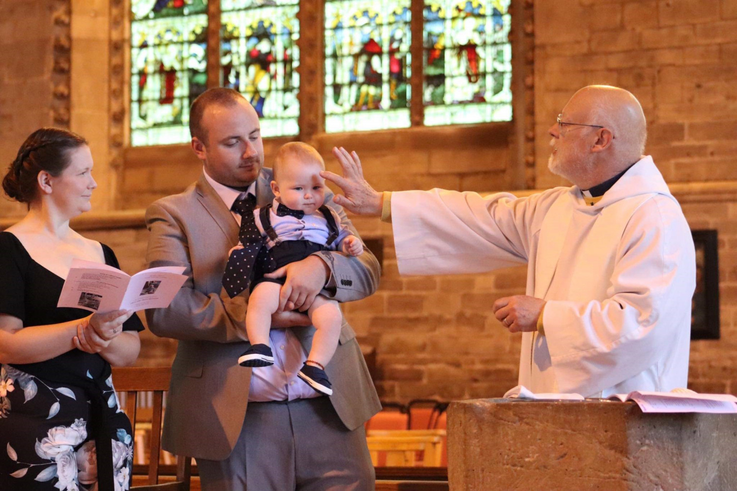 Family with baby to be baptised being blessed by the Rector