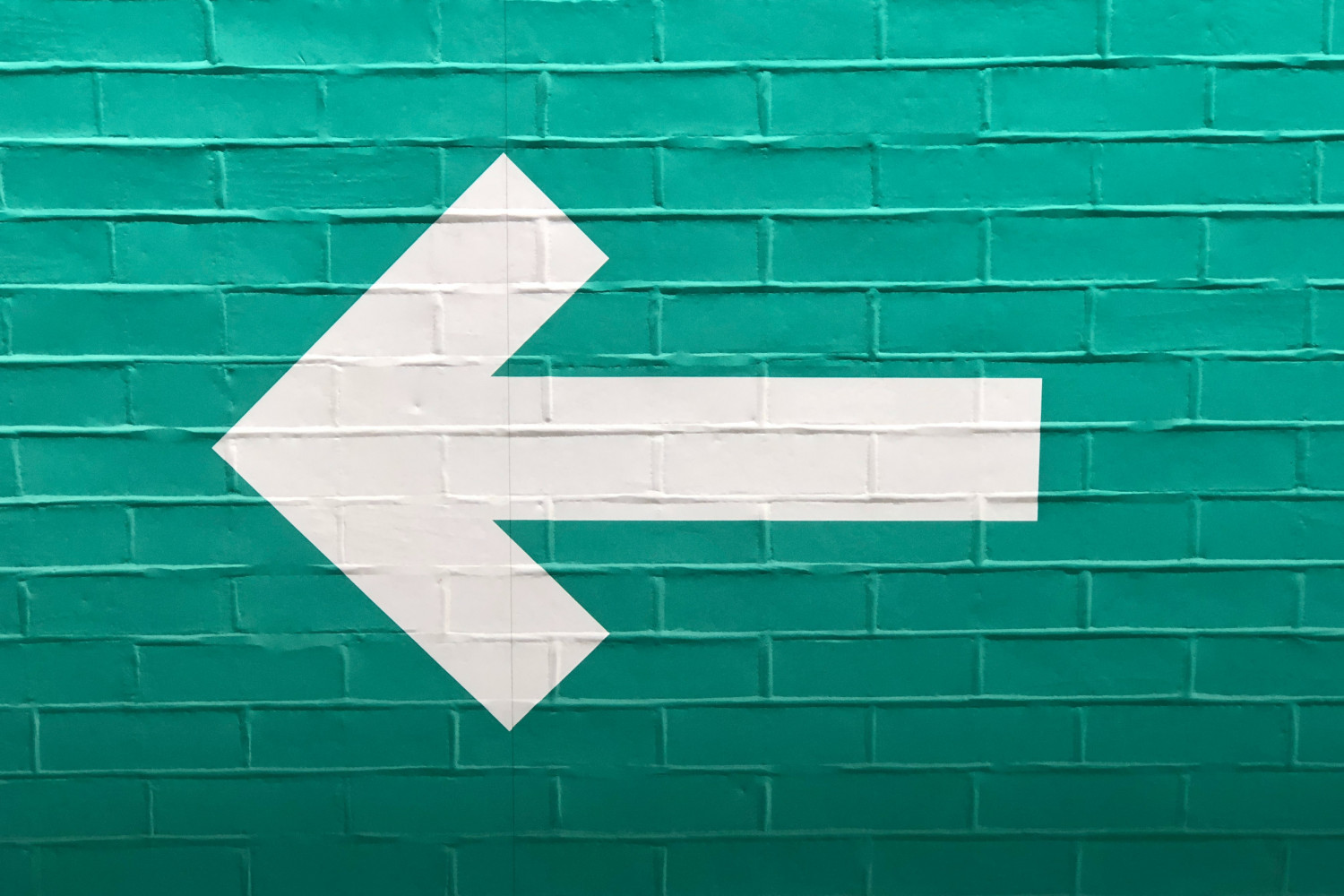 Image of a giant white arrow on a green painted brick wall