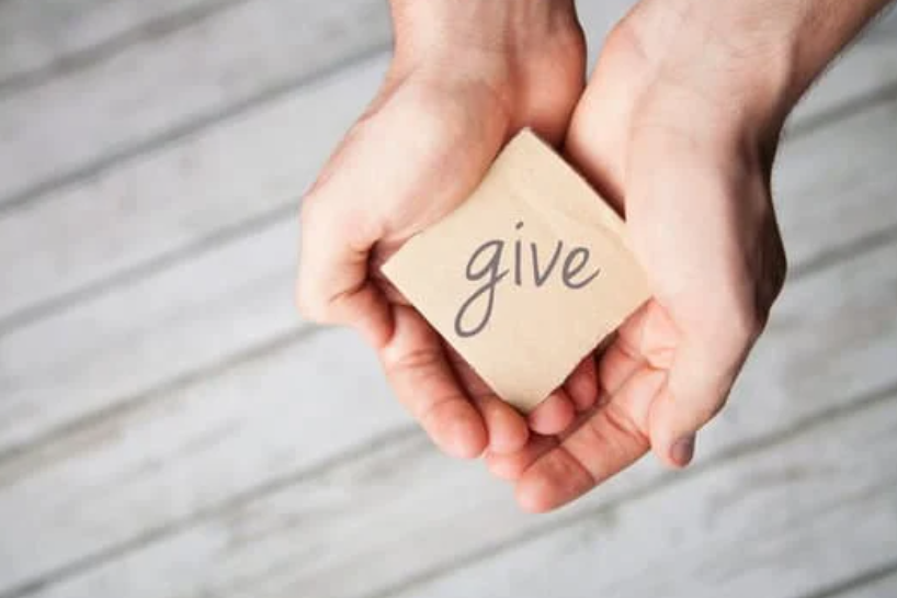Image of a hands cupping a post it notes with the word 'give' written on it