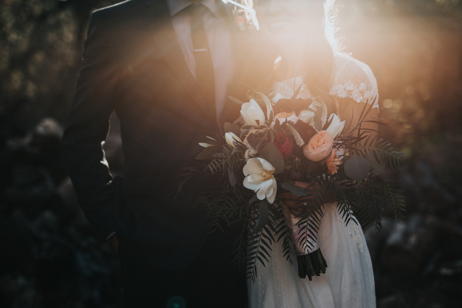 Image of a bride and groom holding a bouquet of flowers