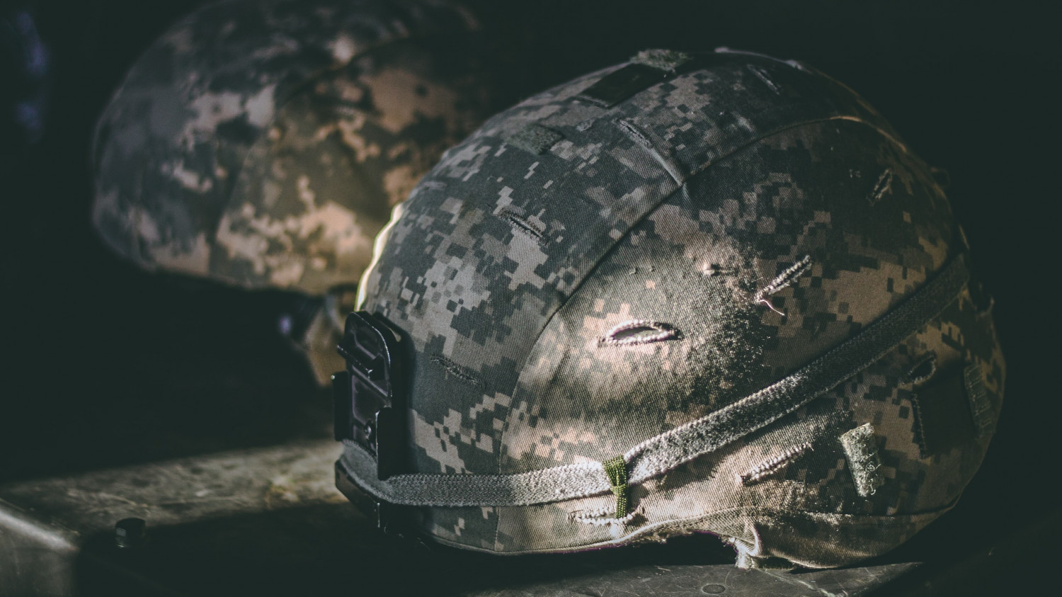 Image of a soldiers helmet on a camp bed