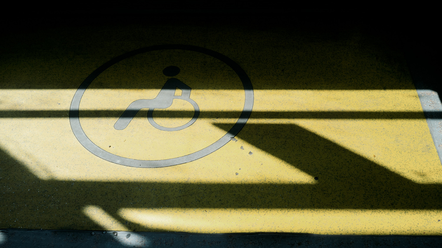 Image of a disability sign painted on a concrete floor