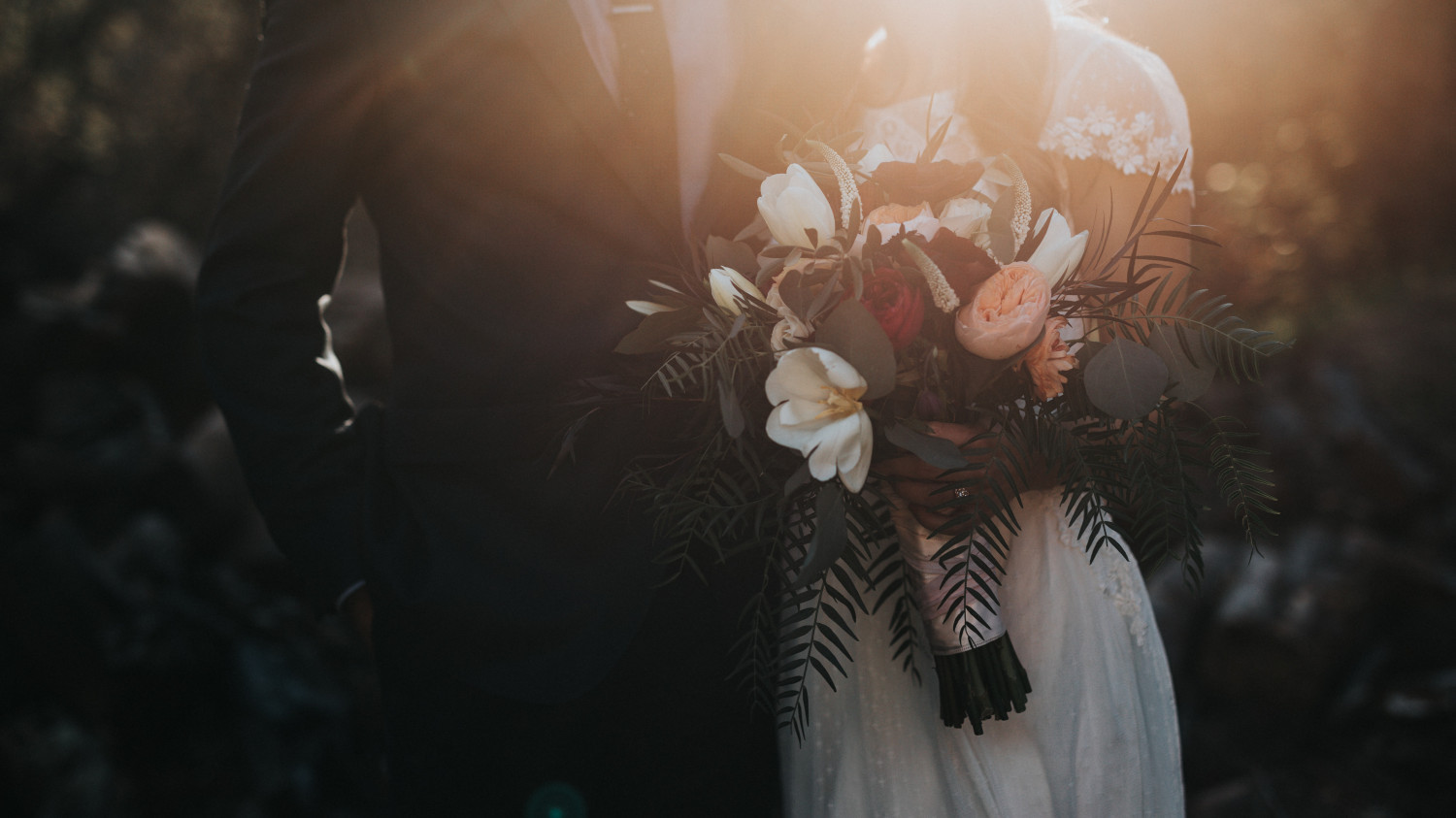 Image of a bride and groom holding a wedding bouquet