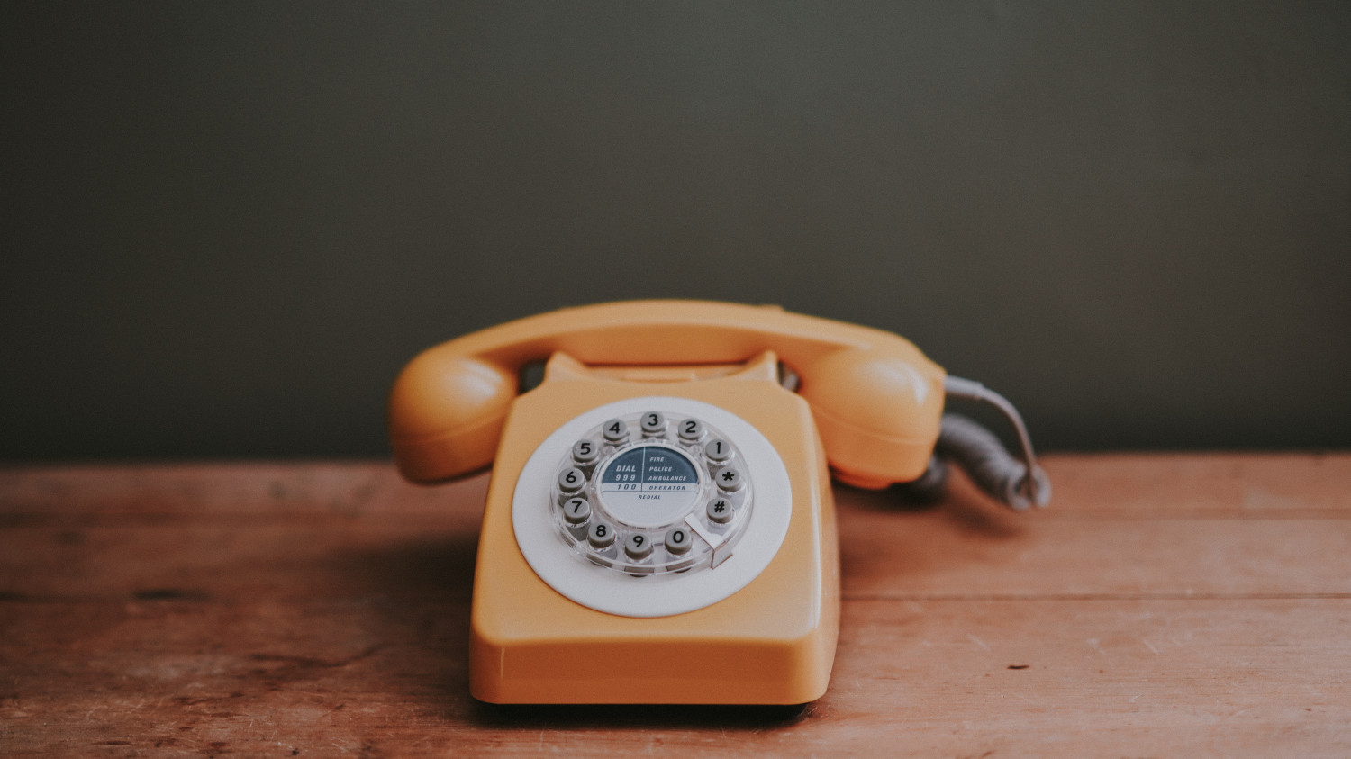 Image of an orange rotary phone on a wooden desk