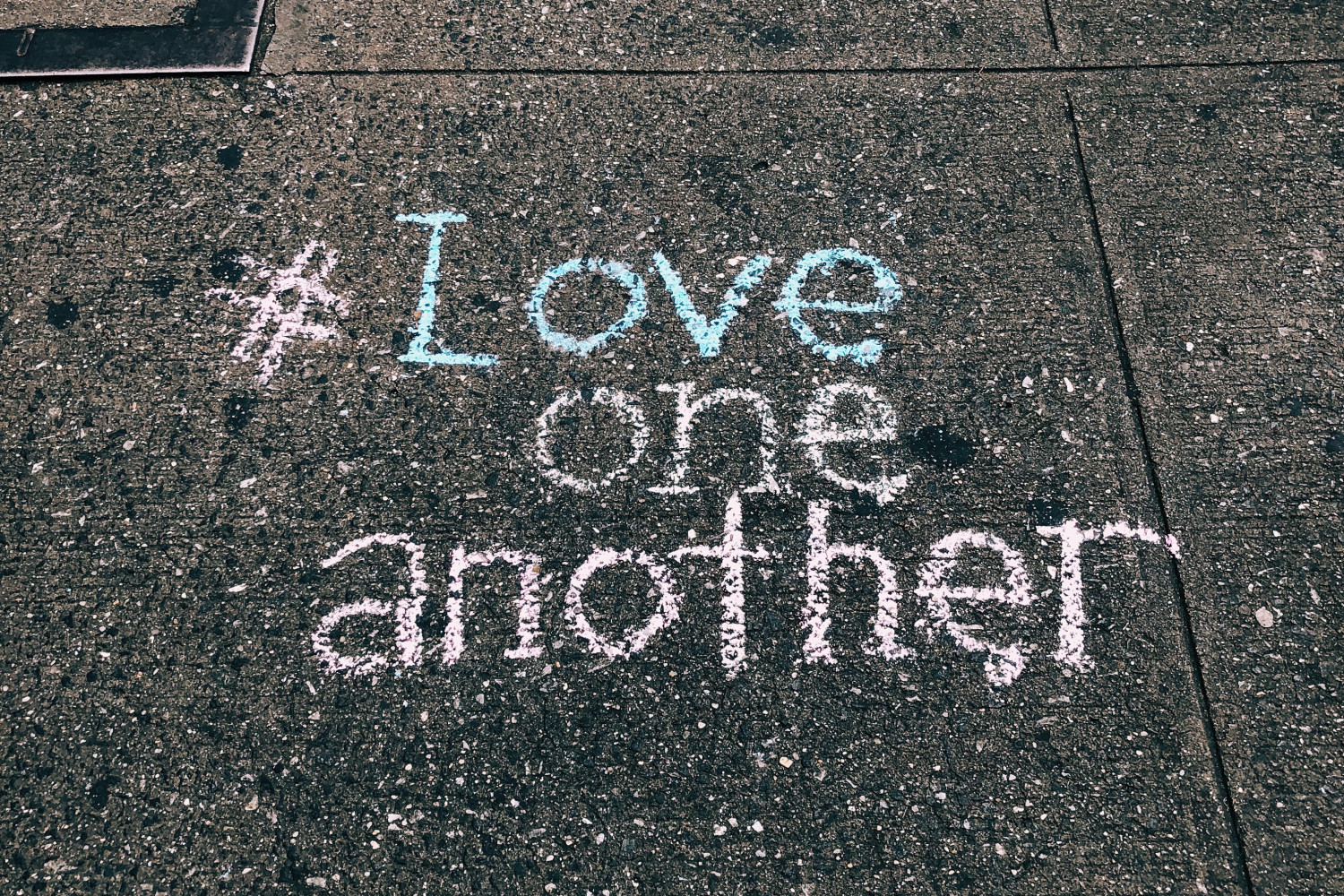 Image of pavement with 'Love one another' written in chalk