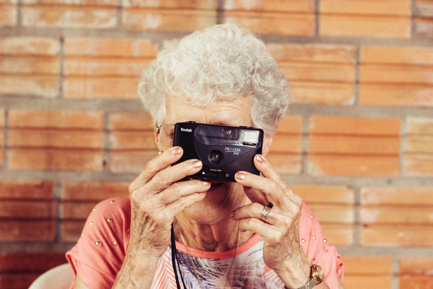 Image of an elderly woman holding up a camera to her face
