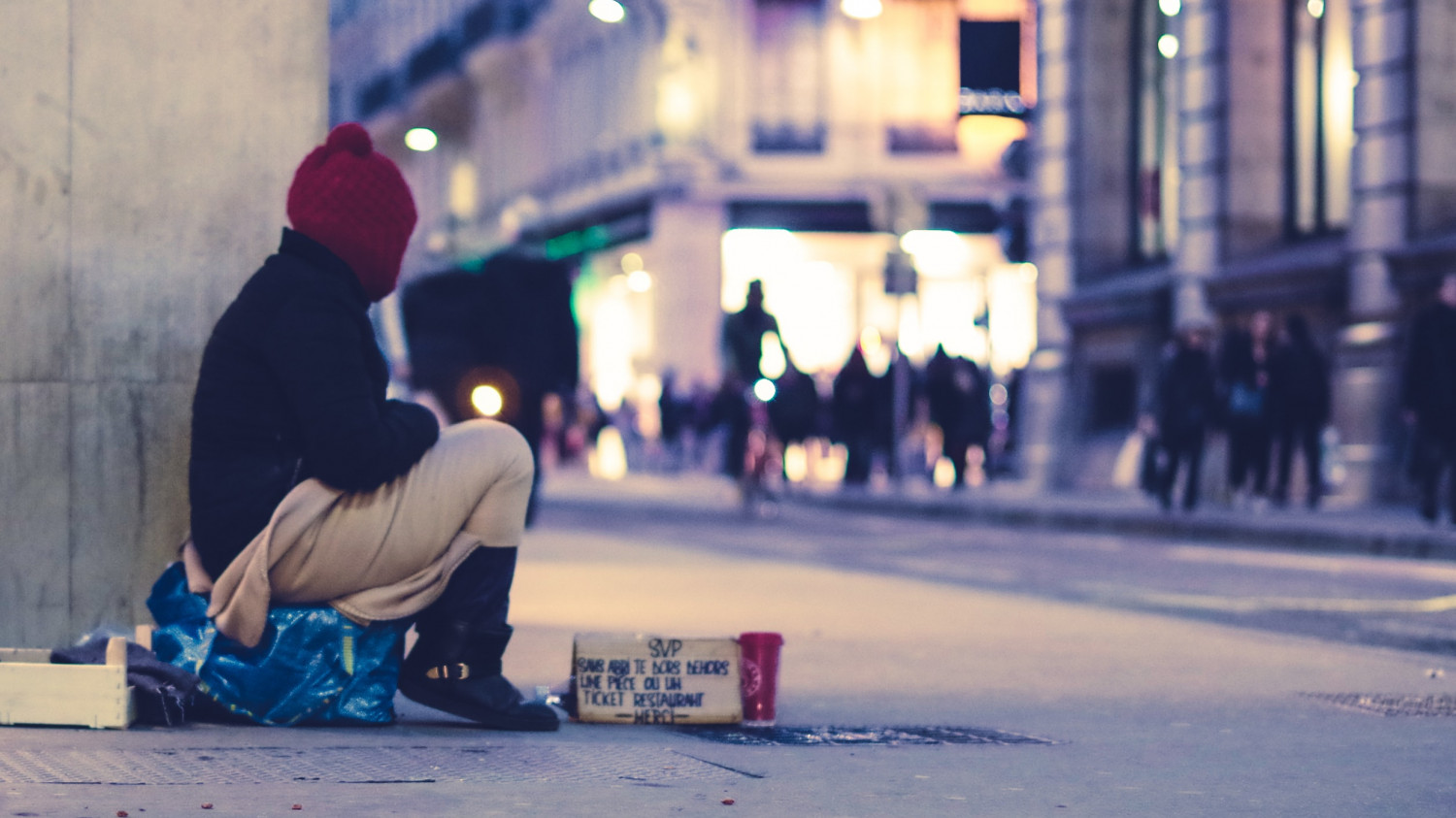Image of a homeless woman seated on a cardboard box in a busy highstreet