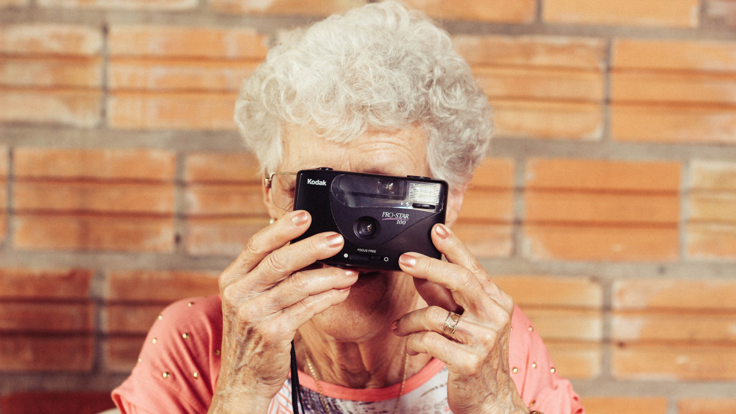 Image of an elderly woman with a camera held up to her face taking a photo