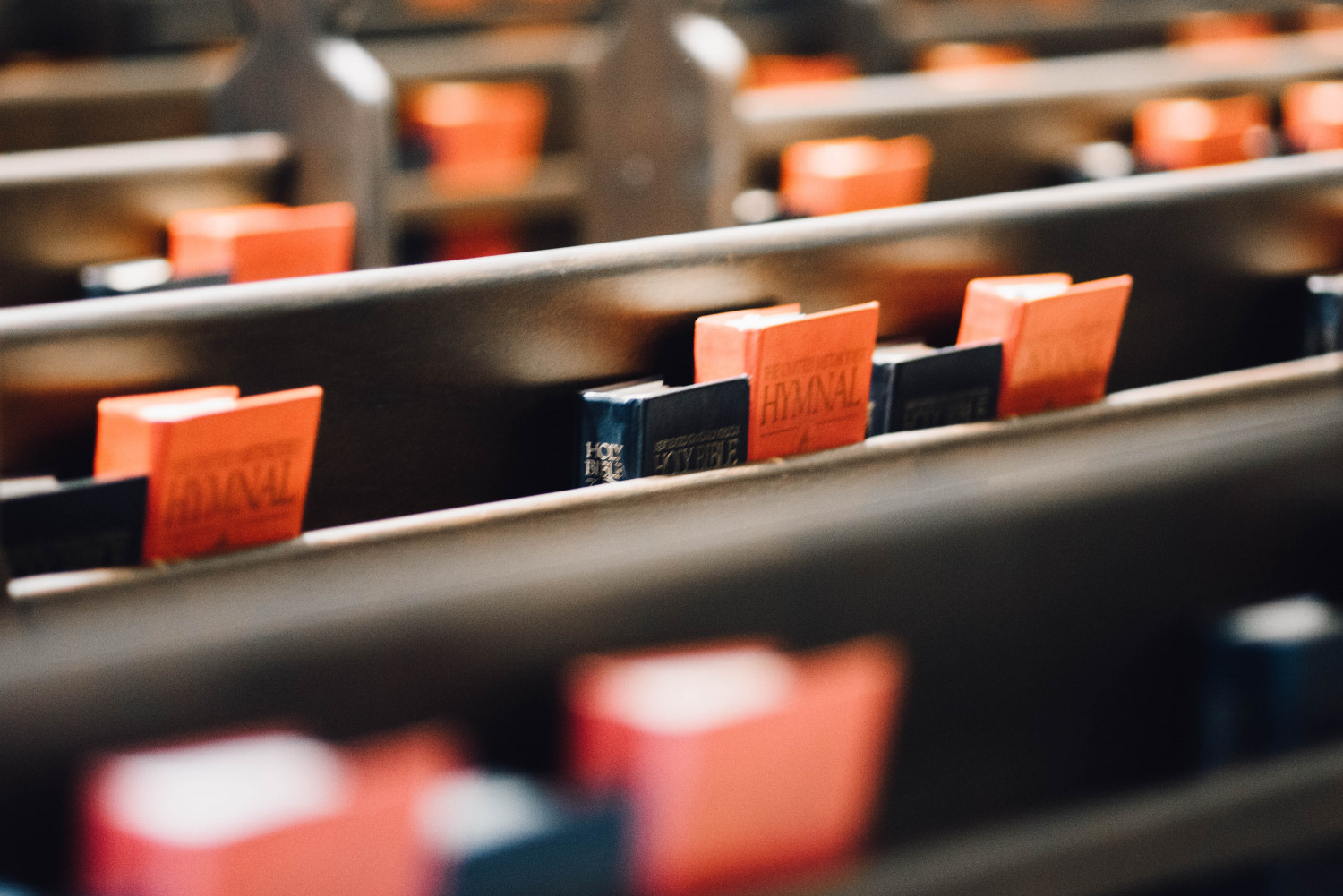 Image of church pews with bibles and psalm books.