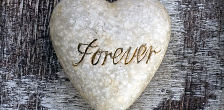 Black wooden frame with a white stone heart with the word Forever carved into the stone