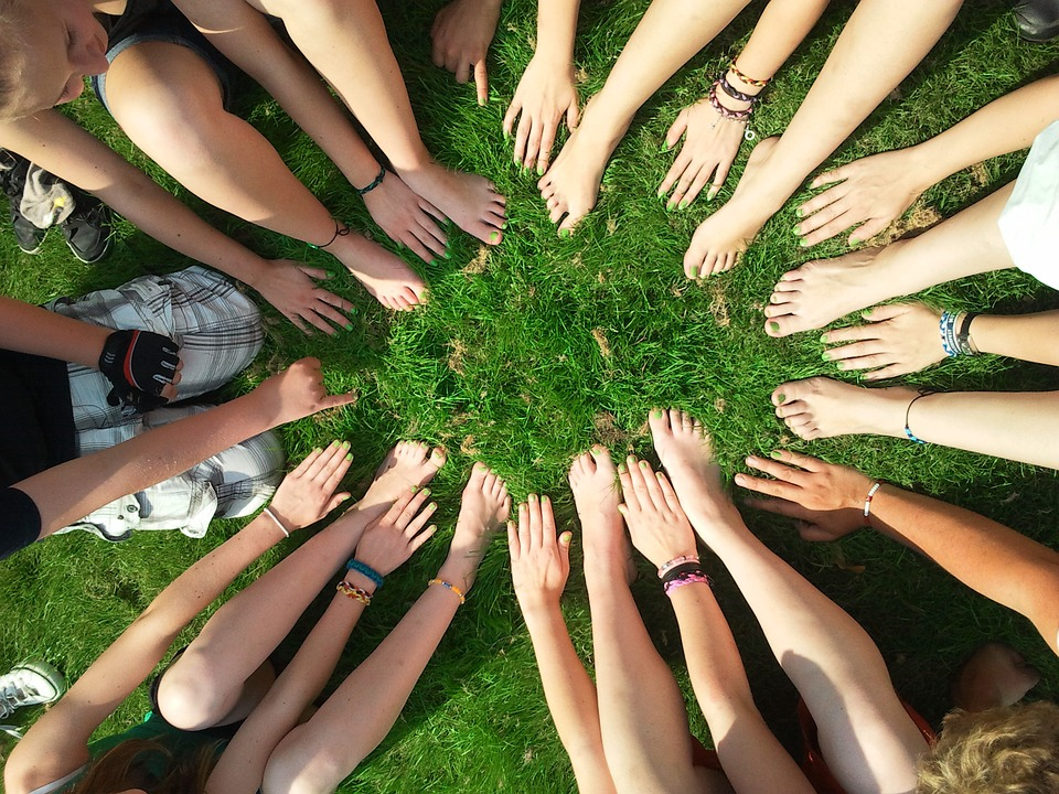 hands all together in a circle on grass