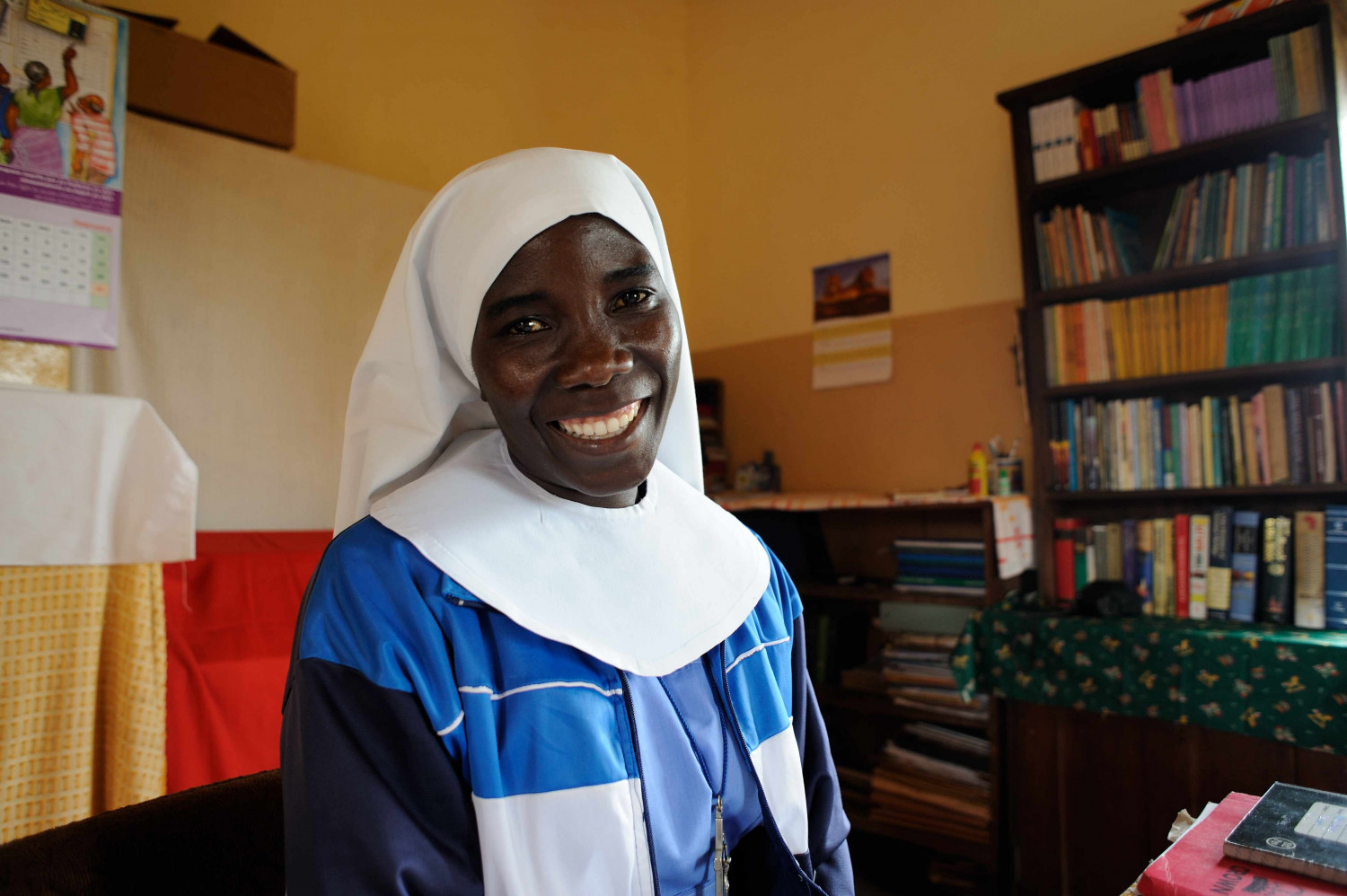 A nun in Tanzania next to a bookshelf